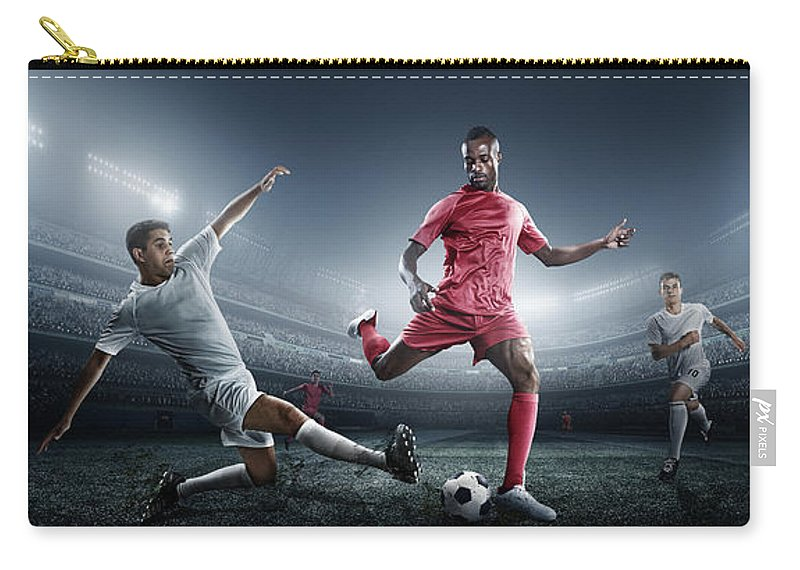 Soccer Uniform Carry-all Pouch featuring the photograph Soccer Player Kicking Ball In Stadium by Dmytro Aksonov