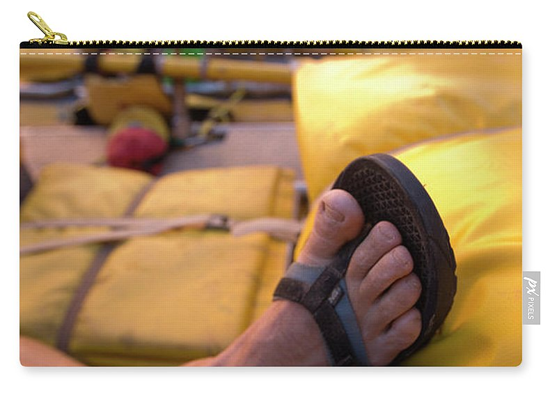 Action Carry-all Pouch featuring the photograph A Persons Crossed Feet In Sandals by Corey Rich