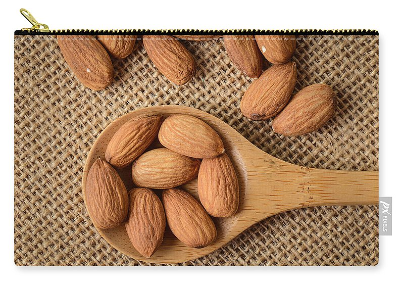 Macro Carry-all Pouch featuring the photograph Almonds On A Spoon With Brown Background by Brandon Bourdages
