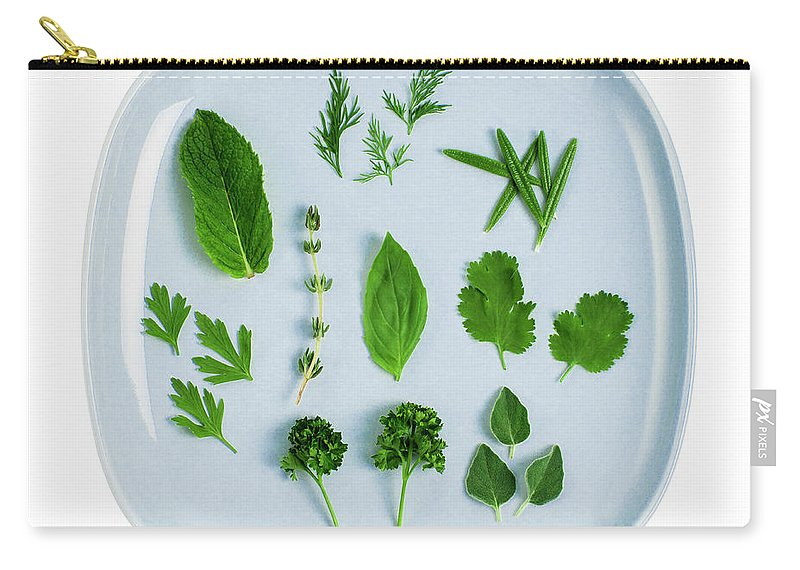 White Background Carry-all Pouch featuring the photograph Assorted Fresh Herb Leaves On Blue Plate by Creative Crop