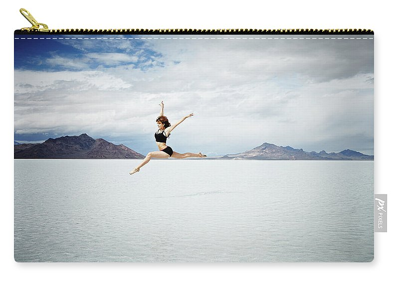 Ballet Dancer Carry-all Pouch featuring the photograph Ballerina Leaping In Mid-air Over Lake by Thomas Barwick
