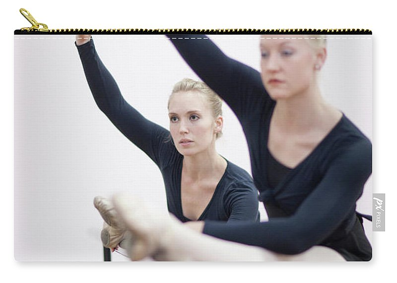 Ballet Dancer Carry-all Pouch featuring the photograph Female Ballerinas Stretching At The by Zero Creatives
