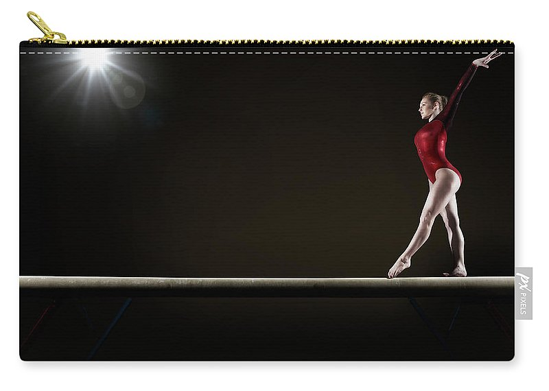 Human Arm Carry-all Pouch featuring the photograph Female Gymnast Balancing On Beam by Mike Harrington