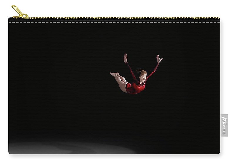 Focus Carry-all Pouch featuring the photograph Female Gymnast Soaring Through Air by Mike Harrington