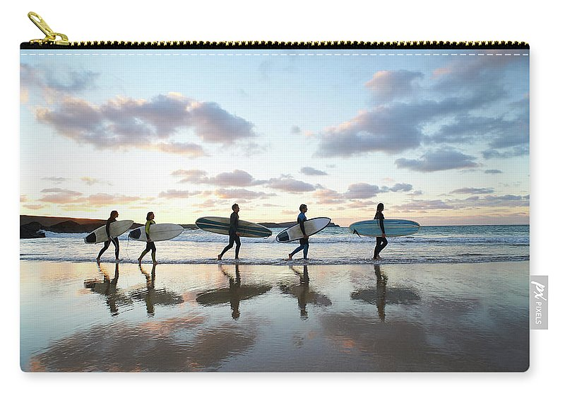 Young Men Carry-all Pouch featuring the photograph Five Surfers Walk Along Beach With Surf by Dougal Waters