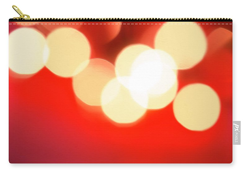 Christmas Lights Carry-all Pouch featuring the photograph Glowing Light On Red Background, Studio by Tetra Images
