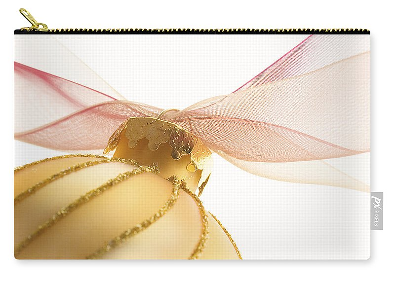 Christmas Carry-all Pouch featuring the photograph Golden Ornament With Red Ribbon High Key by Carol Leigh