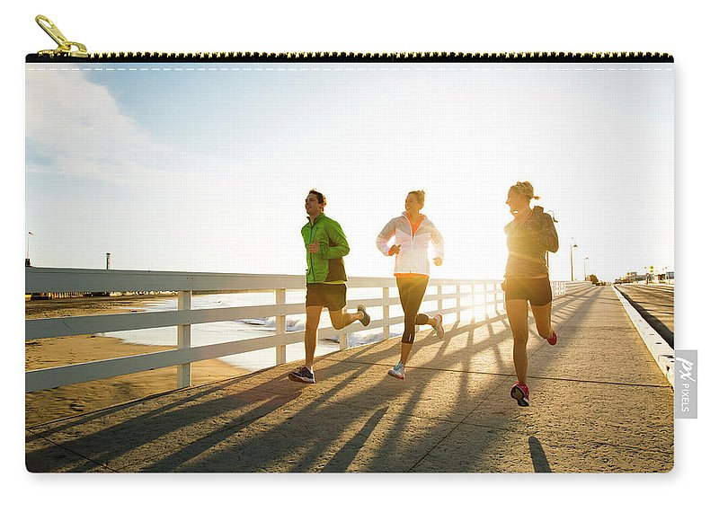 Young Men Carry-all Pouch featuring the photograph Jogging Along The Coast by Jordan Siemens