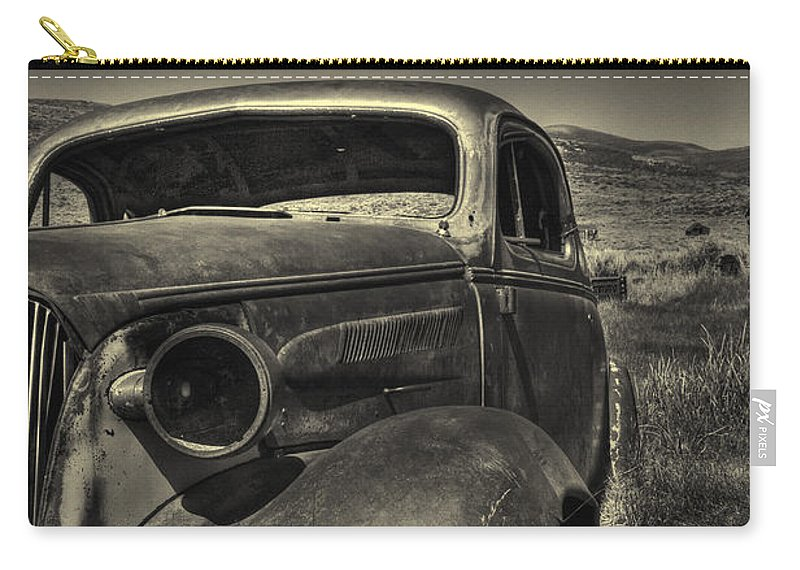 Old; Car; Vintage; Auto; Automobile; Detail; Rust; Grill; Vehicle; Antique; Transportation; Parked; Motor; Front; Engine; Design; Lines; Decal; Metal; Iron; Lights; Desert; Deserted; Abandoned; Windshield; Dirty; Grunge; Sepia Carry-all Pouch featuring the photograph Left In The Hills by Margie Hurwich