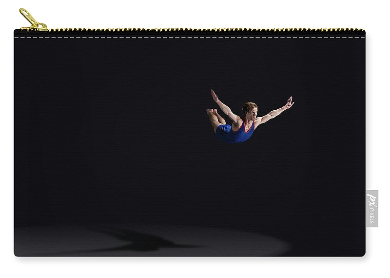 Expertise Carry-all Pouch featuring the photograph Male Gymnast Soaring Through The Air by Mike Harrington