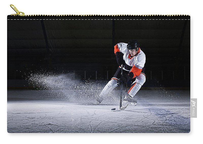 Focus Carry-all Pouch featuring the photograph Male Ice Hockey Player Taking Puck by Mike Harrington