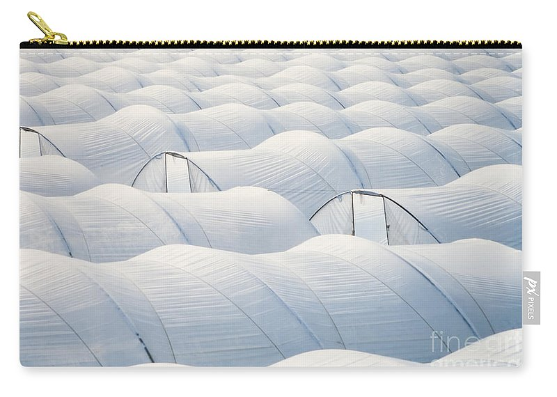 Agriculture Carry-all Pouch featuring the photograph Plastic Sheet Greenhouses To Grow Veggies by Stephan Pietzko