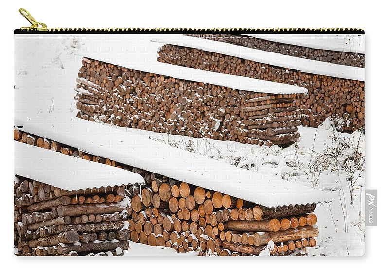 Alternate Carry-all Pouch featuring the photograph Renewable Heat Source Firewood Stacked In Winter by Stephan Pietzko