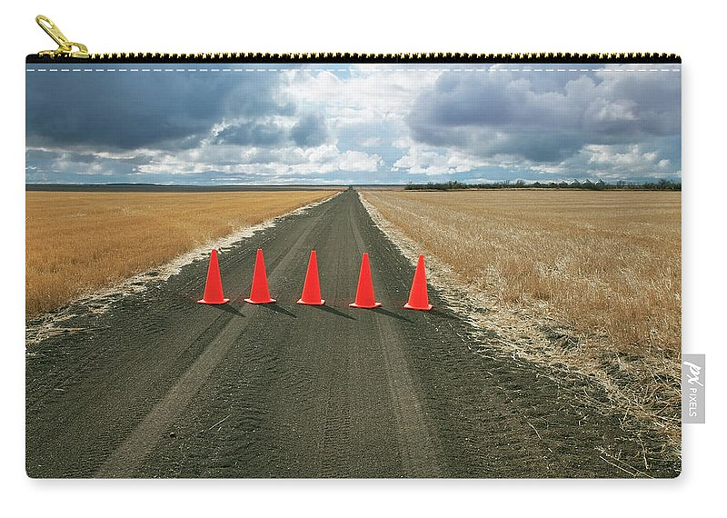 Orange Color Carry-all Pouch featuring the photograph Safety Cones Lined Up Across A Rural by Benjamin Rondel / Design Pics