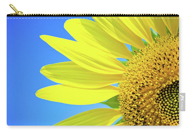 Clear Sky Carry-all Pouch featuring the photograph Sunflower Against Blue Sky by N. Umnajwannaphan