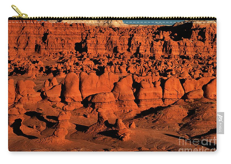 North America Carry-all Pouch featuring the photograph Sunset Light Turns The Hoodoos Blood Red In Goblin Valley State Park Utah by Dave Welling
