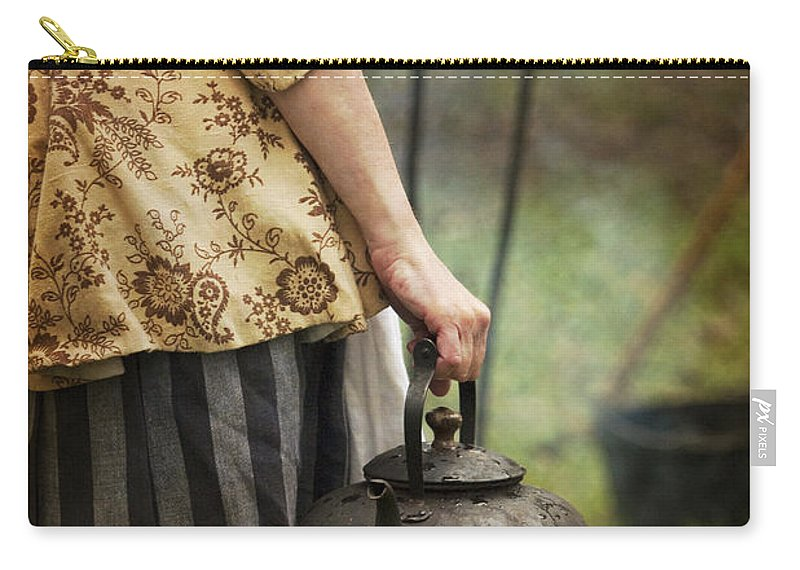 Woman; Caucasian; Lady; Female; Back; Dress; Skirt; Turned Away; Revolutionary; Colonial; Working; Mother; Wife; Kettle; Fire; Outside; Outdoors; Cooking; Pit; Pot; Iron; Metal; Holding; Hand; Apron Carry-all Pouch featuring the photograph The Kettle by Margie Hurwich