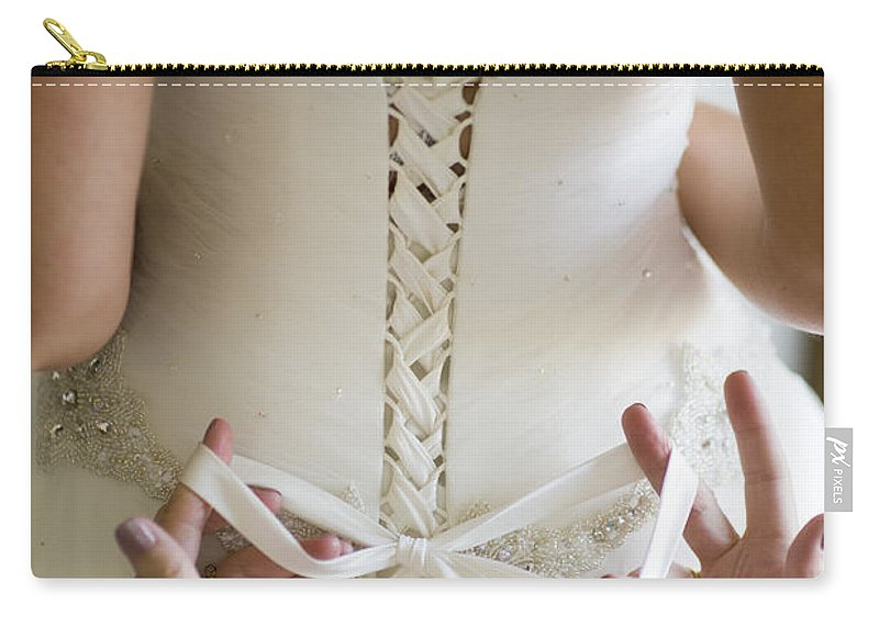 Tie Carry-all Pouch featuring the photograph Tying The Wedding Dress by Lee Avison