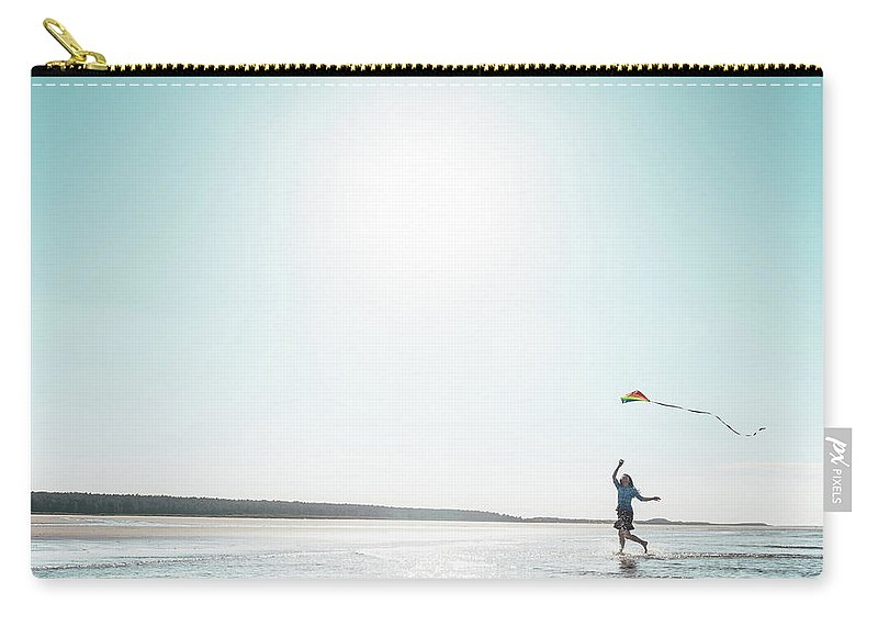 Three Quarter Length Carry-all Pouch featuring the photograph Woman Flying Kite On Beach by Dan Brownsword