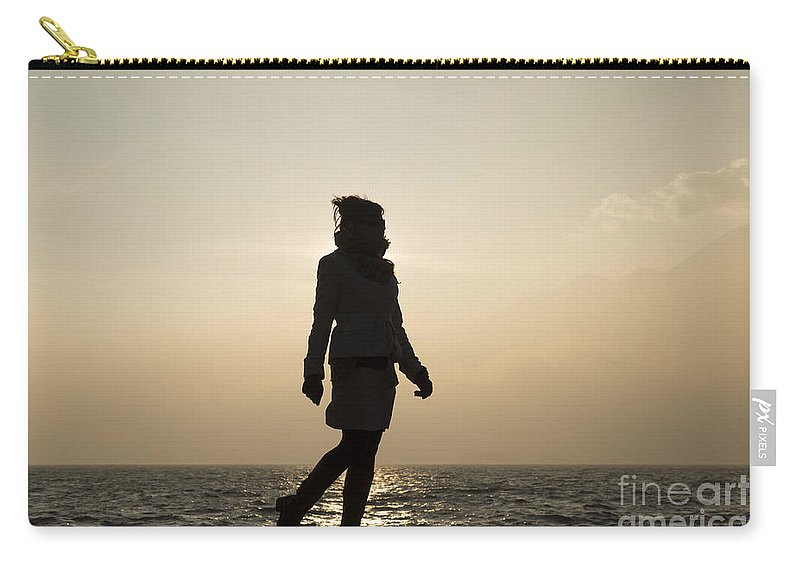 Woman Carry-all Pouch featuring the photograph Woman Walking On The Lake Front by Mats Silvan