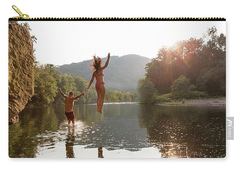 Young Men Carry-all Pouch featuring the photograph Young Couple Jumping Into River by Zave Smith