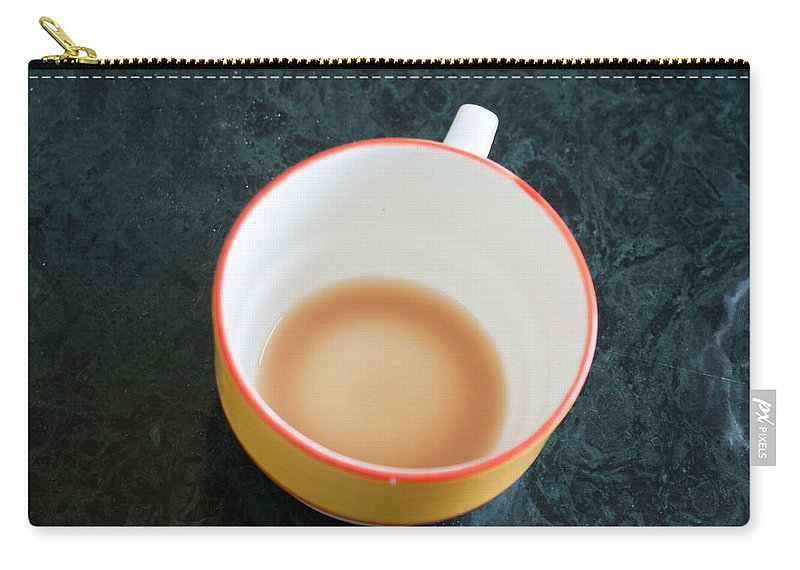 Cup Carry-all Pouch featuring the photograph A Cup With The Remains Of Tea On A Green Table by Ashish Agarwal