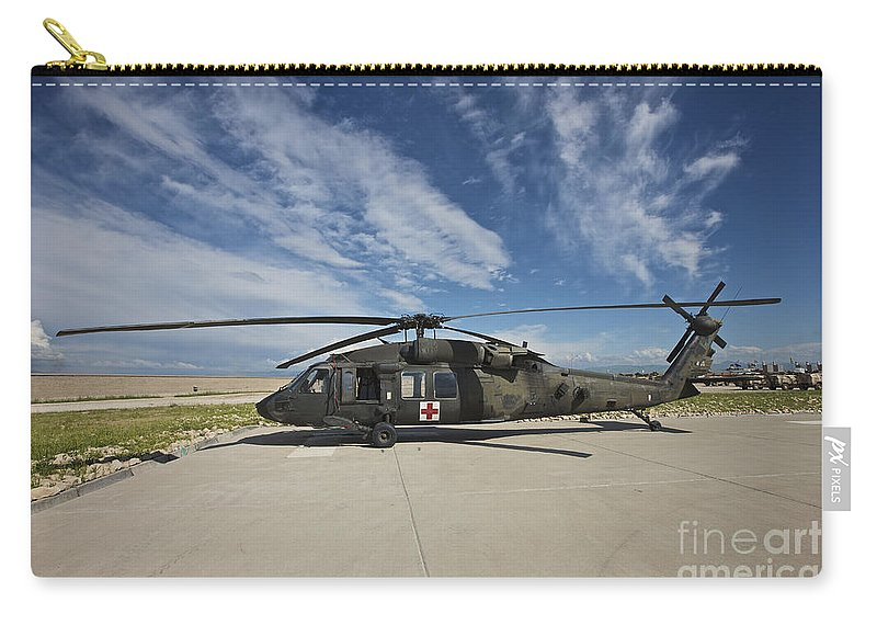 Blackhawk Carry-all Pouch featuring the photograph A Uh-60l Blackhawk Parked On Its Pad by Terry Moore