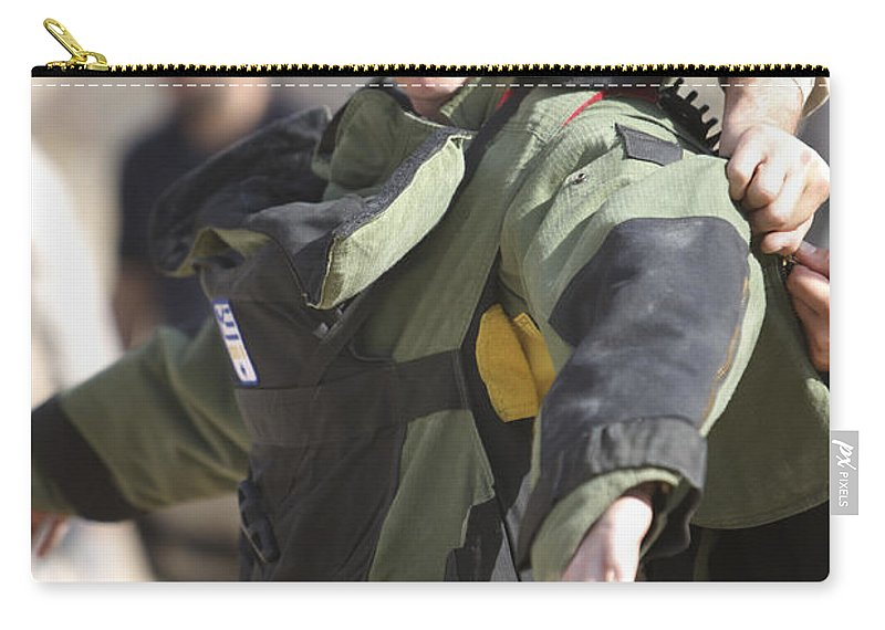 Operation Enduring Freedom Carry-all Pouch featuring the photograph A U.s. Marine Gets Suited by Terry Moore