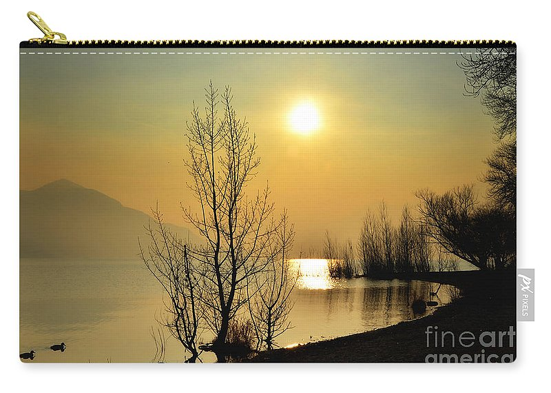 Tree Carry-all Pouch featuring the photograph Sunlight Over A Lake by Mats Silvan