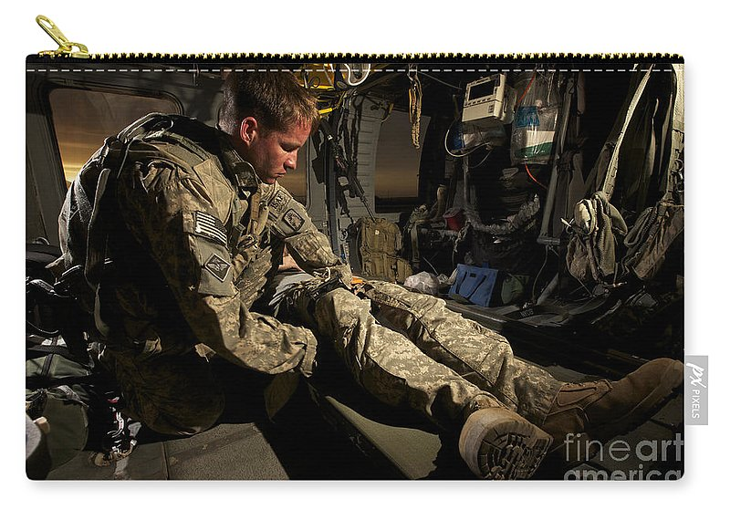 Us Army Carry-all Pouch featuring the photograph U.s. Army Specialist Practices Giving by Terry Moore