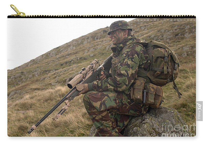 Foreign Military Carry-all Pouch featuring the photograph A British Soldier Armed With A Sniper by Andrew Chittock