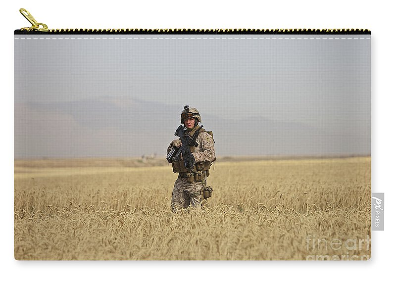 Patrol Carry-all Pouch featuring the photograph U.s. Marine Patrols A Wadi Near Kunduz by Terry Moore