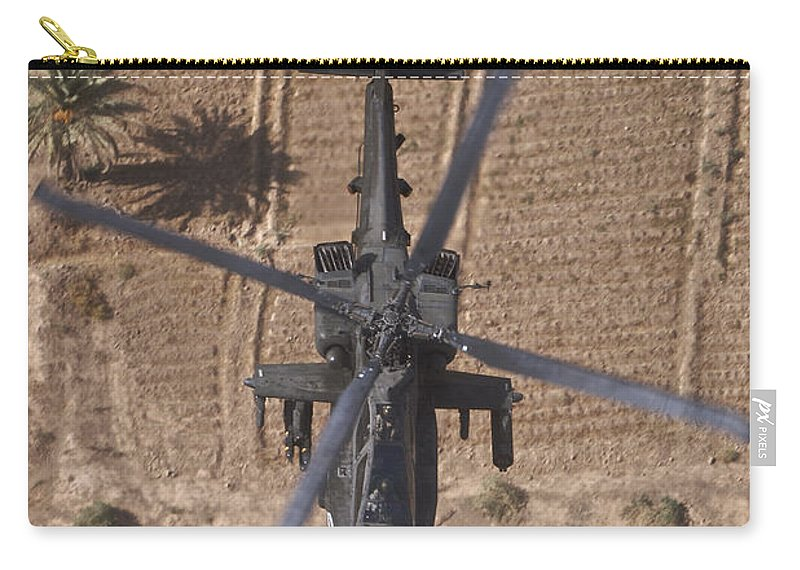 Ah-64 Carry-all Pouch featuring the photograph An Ah-64d Apache Helicopter In Flight by Terry Moore