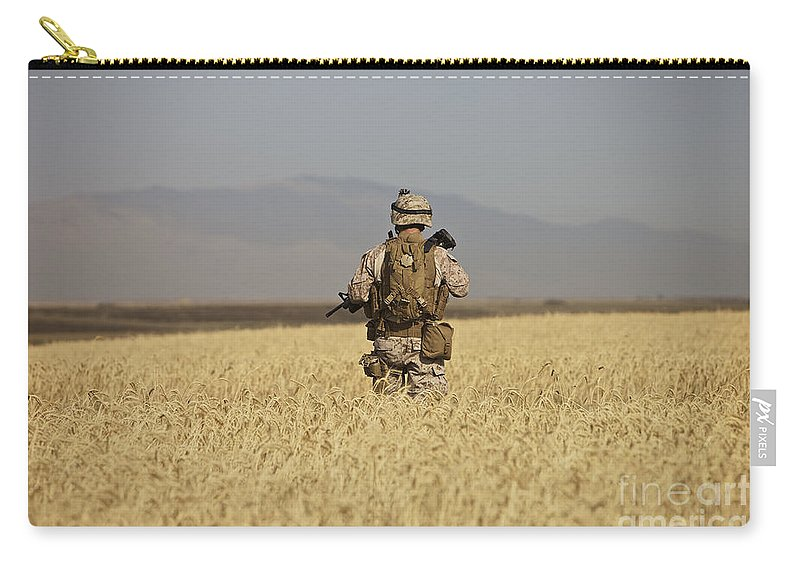 Wheat Carry-all Pouch featuring the photograph U.s. Marine Patrols A Wadi Near Kunduz by Terry Moore