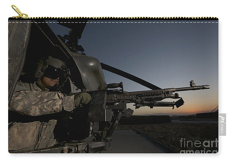Helicopter Carry-all Pouch featuring the photograph A Uh-60l Blackhawk Door Gunner Mans by Terry Moore