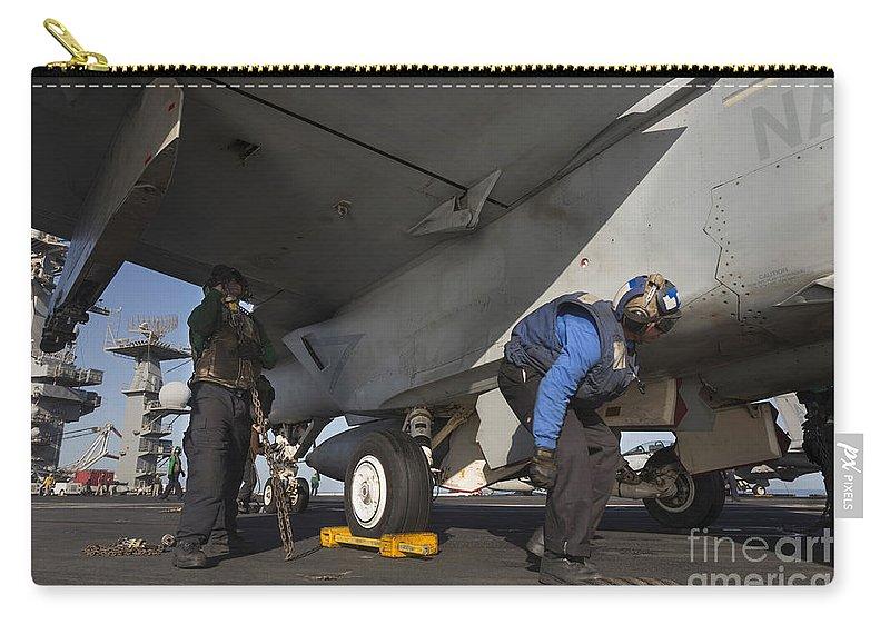 Arabian Sea Carry-all Pouch featuring the photograph Airmen Chain Down An Fa-18e Super by Gert Kromhout