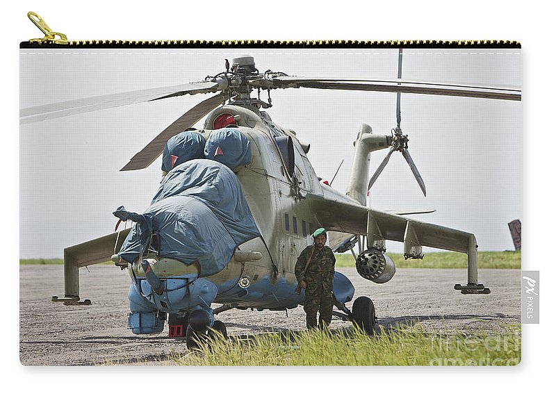 Mil Mi-35 Carry-all Pouch featuring the photograph An Afghan Army Soldier Guards A Mi-35 by Terry Moore