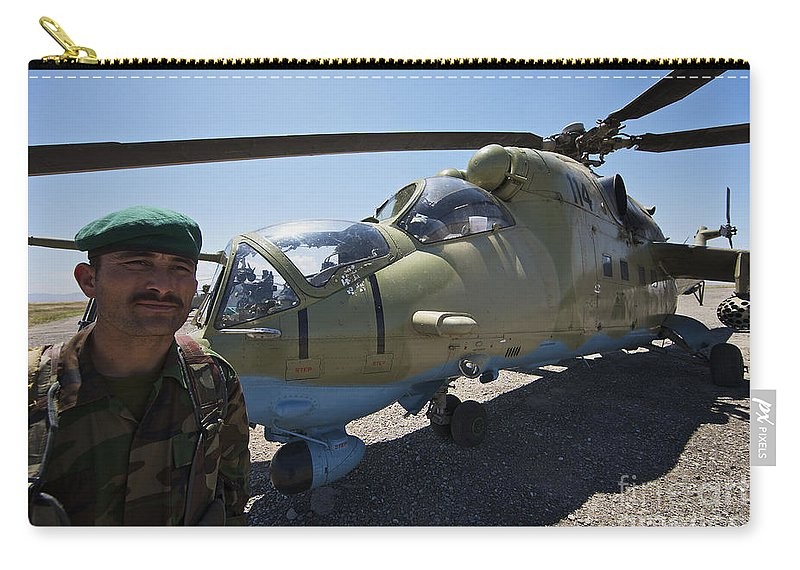 Mil Mi-35 Carry-all Pouch featuring the photograph An Afghan Army Soldier Guards An Mi-35 by Terry Moore