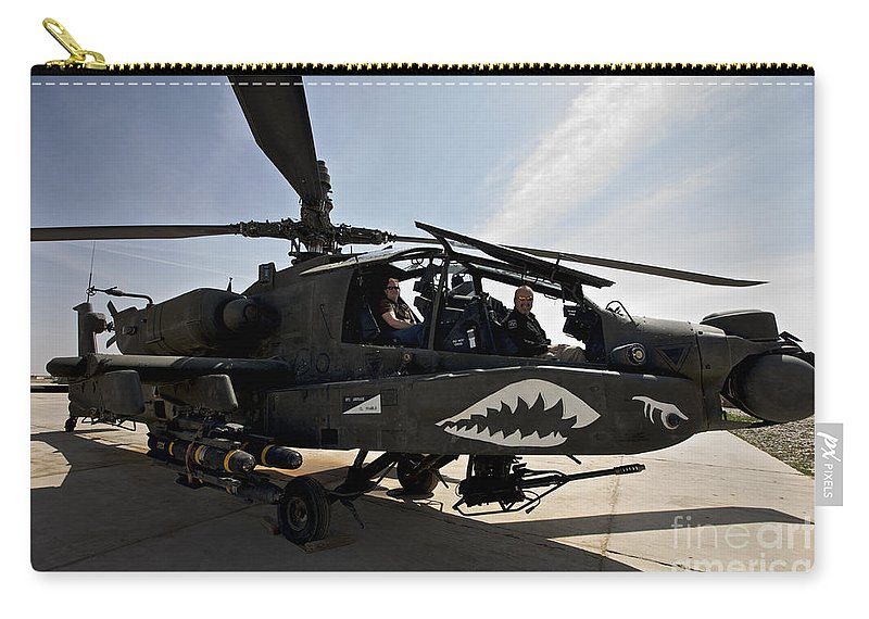 Ah-64 Carry-all Pouch featuring the photograph An Ah-64d Apache Helicopter Parked by Terry Moore
