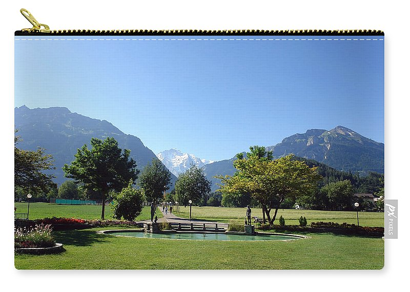 Interlaken Carry-all Pouch featuring the photograph An Open Field In Interlaken With A View Of The Mountains In The Background by Ashish Agarwal