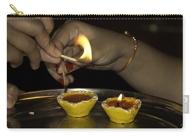 Action Carry-all Pouch featuring the photograph Trying To Light An Oil Lamp That Has Gone Out by Ashish Agarwal