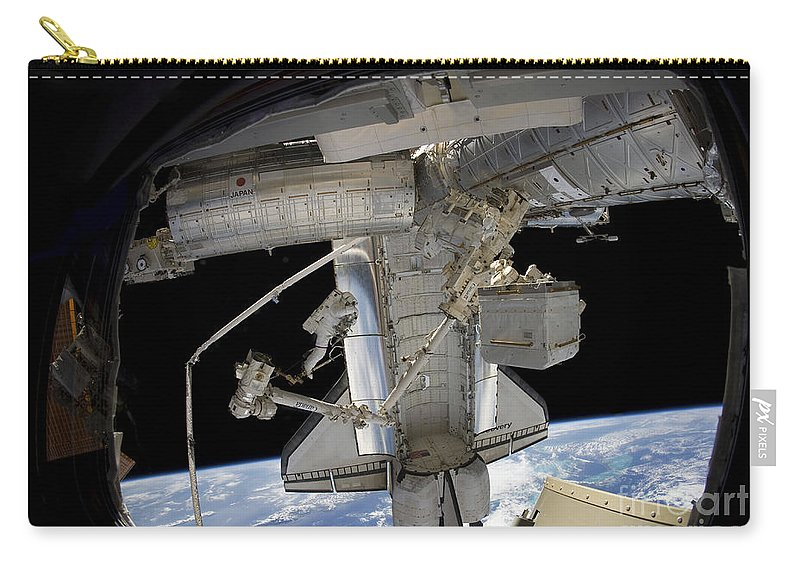View From Space Carry-all Pouch featuring the photograph Astronaut Participates In A Spacewalk by Stocktrek Images