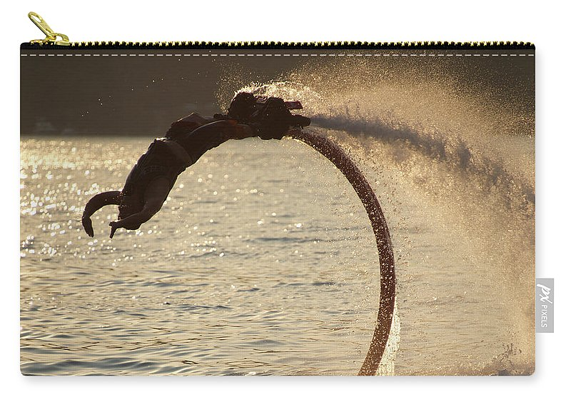 Bodrum Carry-all Pouch featuring the photograph Flyboarder Doing Back Flip Over Backlit Waves by Ndp