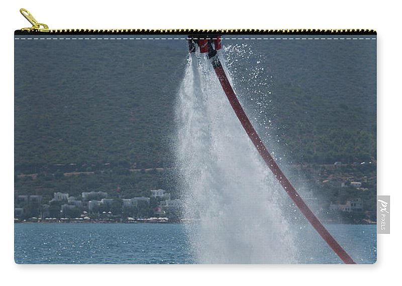 Bodrum Carry-all Pouch featuring the photograph Flyboarder In Silhouette Balancing High Above Water by Ndp