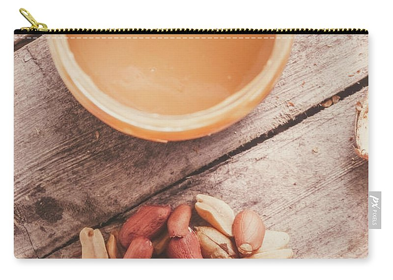 Peanuts Carry-all Pouch featuring the photograph Peanut Butter Jar With Peanuts On Wooden Surface by Jorgo Photography - Wall Art Gallery
