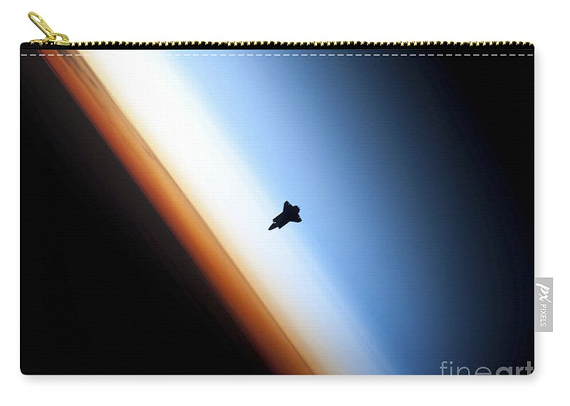 Sts-130 Carry-all Pouch featuring the photograph Silhouette Of Space Shuttle Endeavour by Stocktrek Images