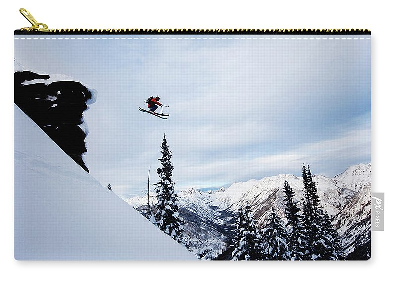 Skiing Carry-all Pouch featuring the photograph A Athletic Skier Jumping Off A Cliff In by Patrick Orton