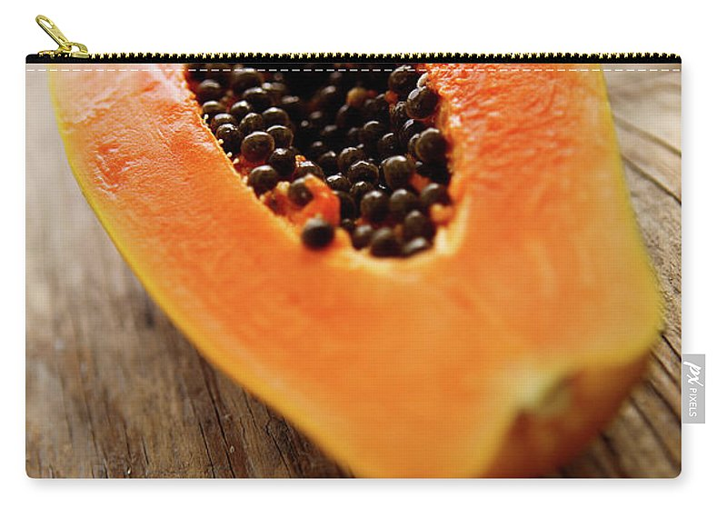 Serving Size Carry-all Pouch featuring the photograph A Halved Fresh Papaya On A Wooden by Chang