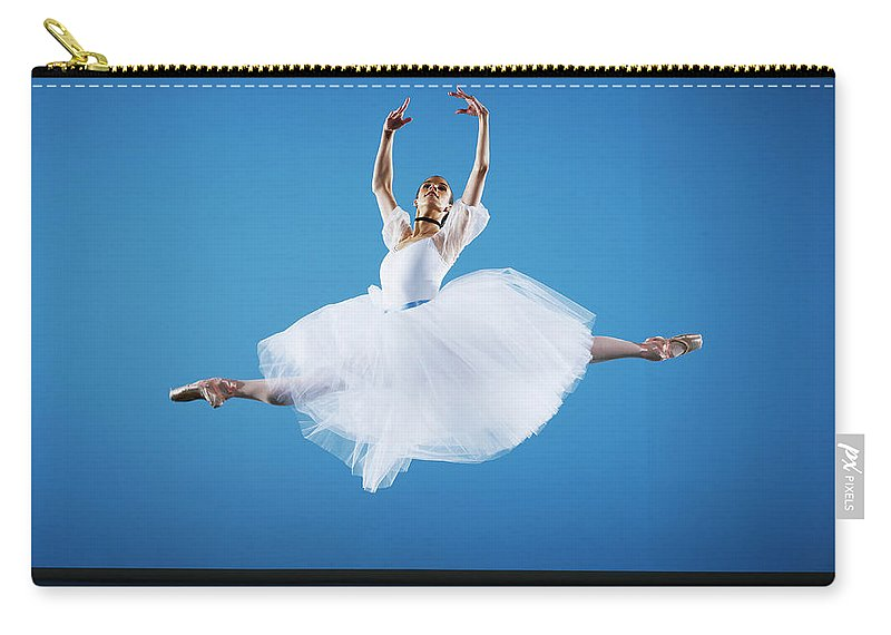 Ballet Dancer Carry-all Pouch featuring the photograph Ballerina Leaping On Stage, Arms Raised by Thomas Barwick