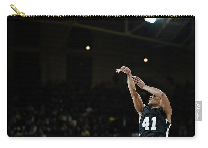 Expertise Carry-all Pouch featuring the photograph Basketball Player Shooting Jump Shot In by Thomas Barwick